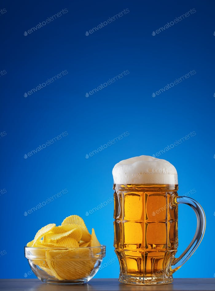 Faceted mug of light beer with foam and chips in plate