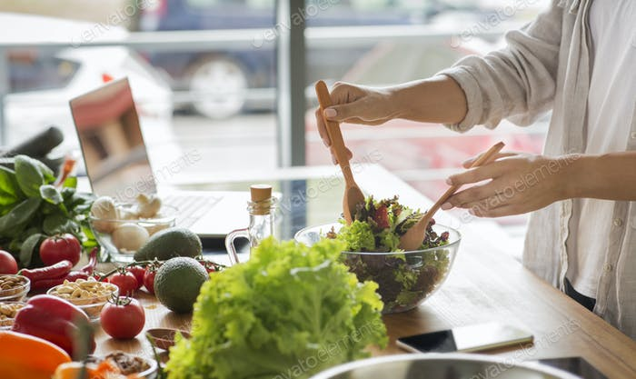Woman mixing delicious superfood salad ingredients in the kitchen