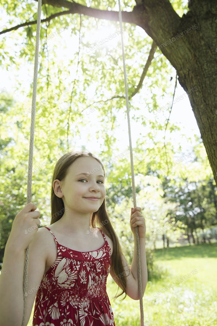 Summer. A girl in a sundress on a swing in an orchard.