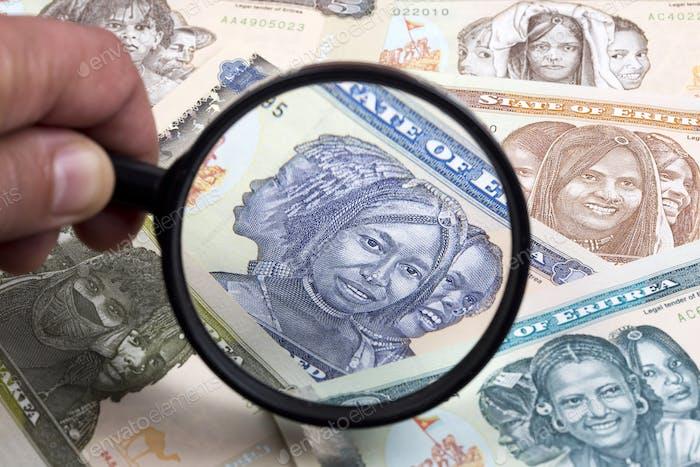 Dinero eritreo en una lupa