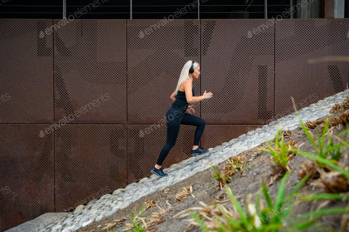 Fit attractive sports women running fast in stairs against a metal wall in city