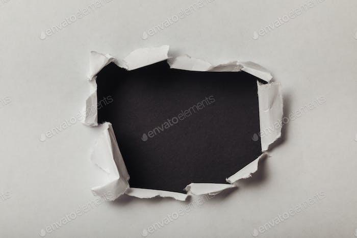 zerrissenes Loch in Blatt Papier auf schwarzem Hintergrund