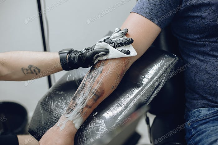 Man doing a tattoo in a tattoo salon