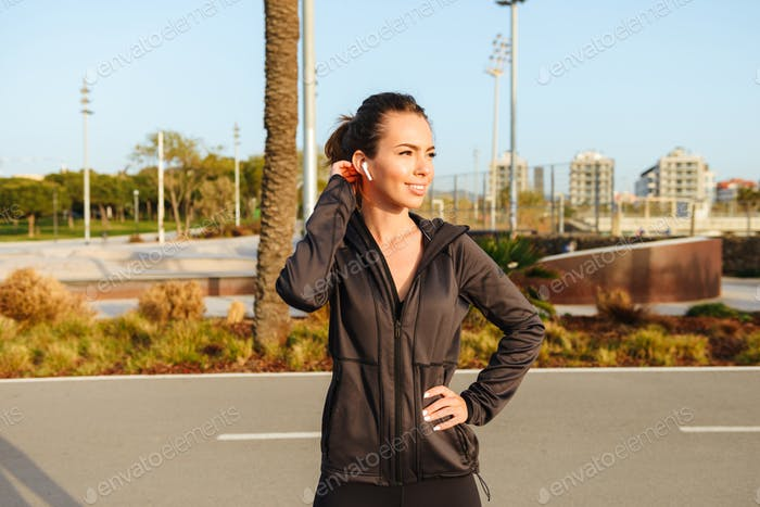 Happy young sports woman standing outdoors