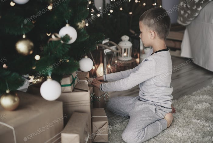 Small boy arranging christmas presents