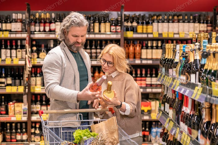 Mature consumers with shopping cart choosing wine while comparing two bottles