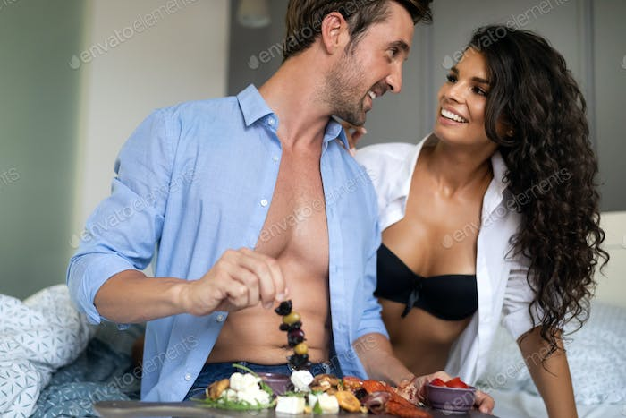 Happy young couple eat breakfast in bedroom in morning