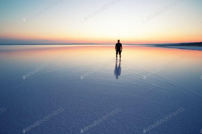 Salt lake Tuz with man leaving at sunset