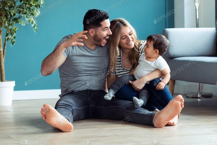 Hübsche junge Eltern spielen mit Babysohn, während sie zu Hause auf dem Boden sitzen.