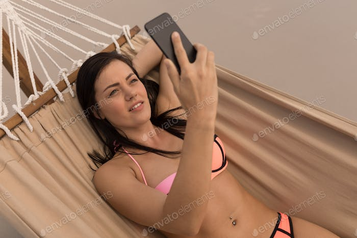 Beautiful young woman taking selfie with mobile phone while relaxing on hammock at beach