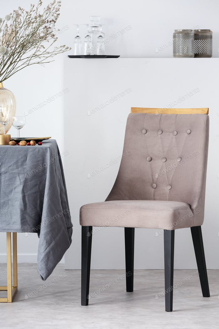 Stylish chair next to dining table with grey tablecloth in trendy dining room interior