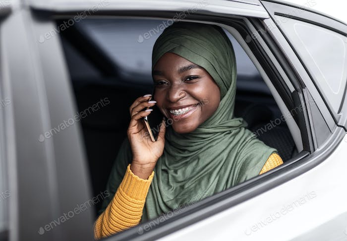 Riding Taxi. Smiling Black Muslim Woman Talking On Cellphone On Car's Backseat