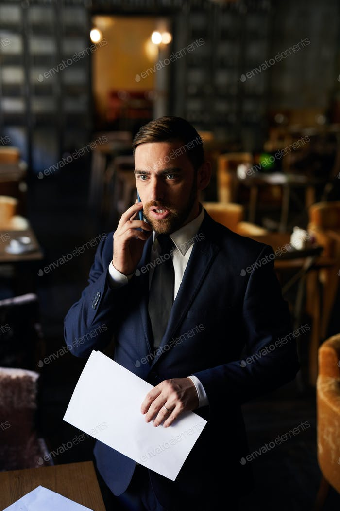 Upset businessman listening to colleague on phone