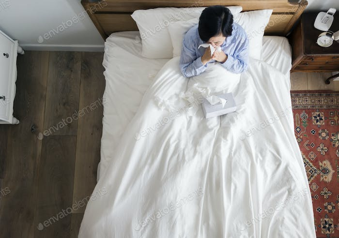 Sick woman on the bed blowing her nose
