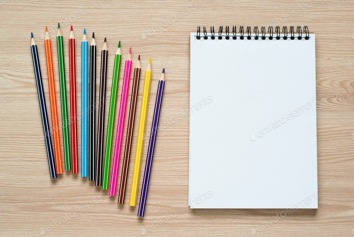 Pencils and notebook on a desk.
