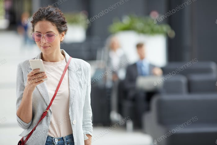 Stylish girl checking phone on move