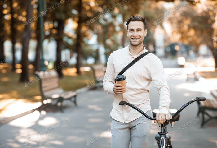 Way to office. Smiling guy with cup of coffee walking with bike
