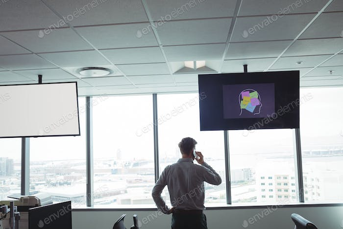 Rear view of businessman taking on mobile phone at office