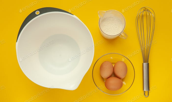 Whisk and a plastic cup for whipping on a yellow background