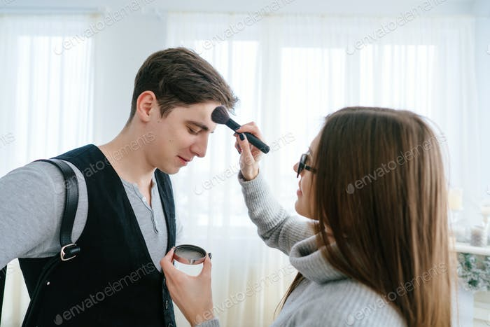 Woman doing makeup guy