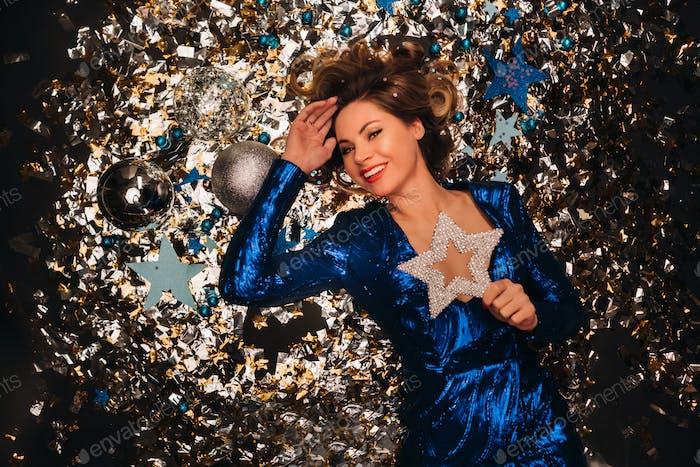 eine Frau in einem blauen Paillettenkleid lächelt und liegt unter einem fallenden bunten Konfetti auf dem Boden