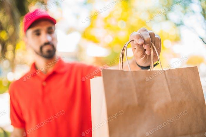 El repartidor que lleva paquetes mientras hace la entrega a domicilio.