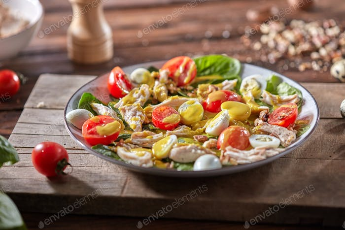 Fresh homemade salad with natural ingredients - organic clean vegetables, chicken meat and guail