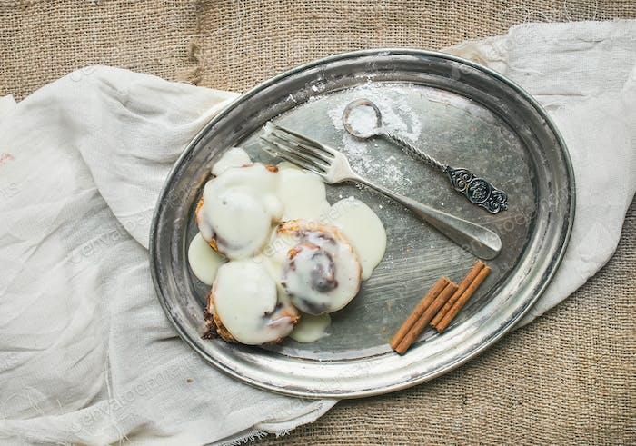 Zimtschnecken mit Sahne-Käse-Zuckerguss und Zimtstangen auf einem