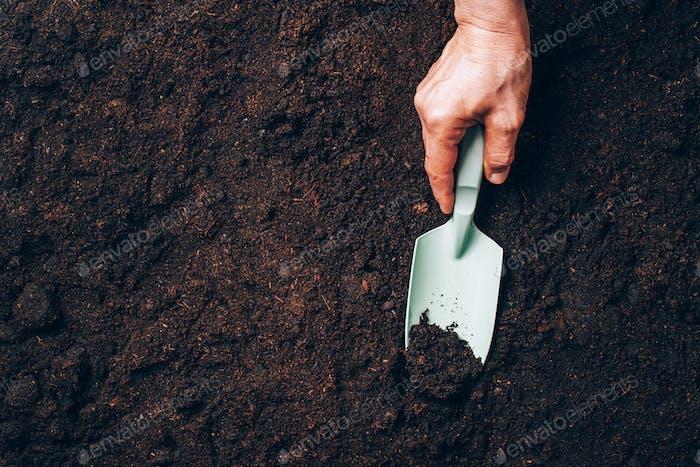 Hand hält Hovel in der Hand über Boden Hintergrund. Landwirtschaft, Bio-Gartenbau, Pflanzung oder