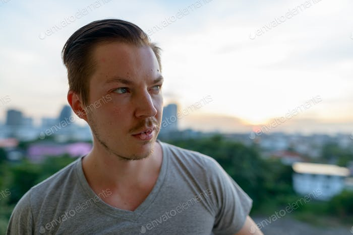 Face of young handsome man thinking against view of the city
