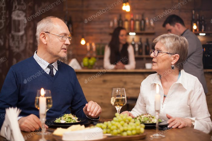 Old Couple enjoying their time together while dining in a vintage restaurant