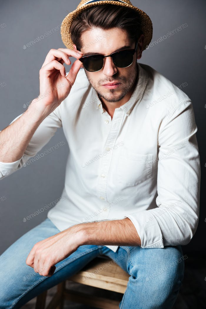 Serious young man in white shirt, jeans, sunglasses and hat