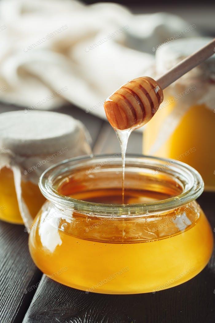 Honey background. Sweet honey in glass jar on wooden background