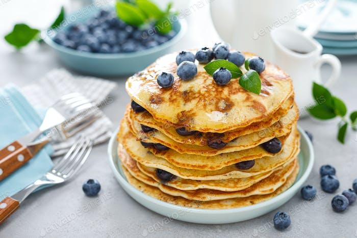 Blaubeerpfannkuchen mit Butter, Ahornsirup und frischen Beeren. Amerikanisches Frühstück