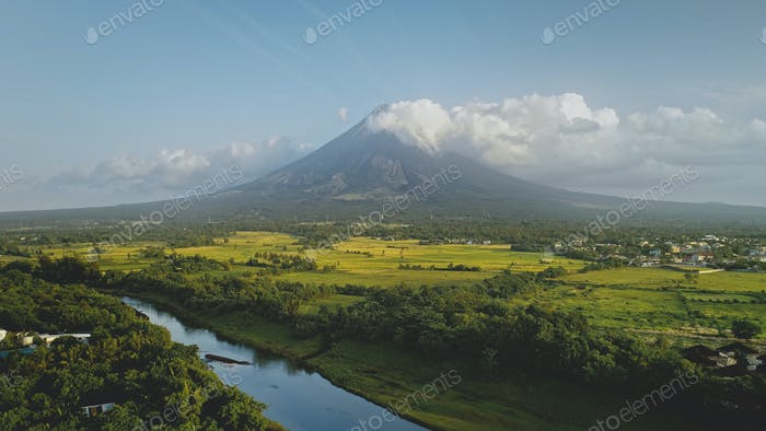 Hillside river at erupt volcano: green grass shore at Philippines countryside aerial. Fields, valley