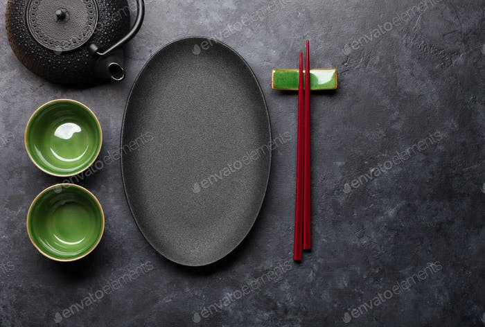 Empty plate, cup, teapot and chopsticks