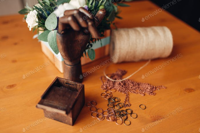 Needlework, metal rings and wooden hand on table