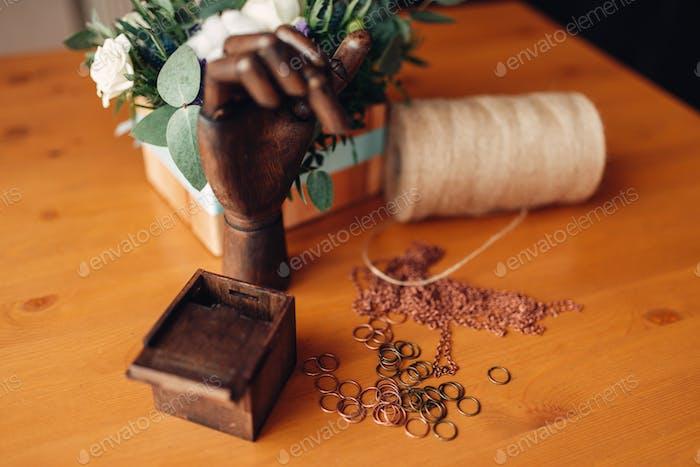 Handarbeit, Metallringe und Holzhand auf dem Tisch