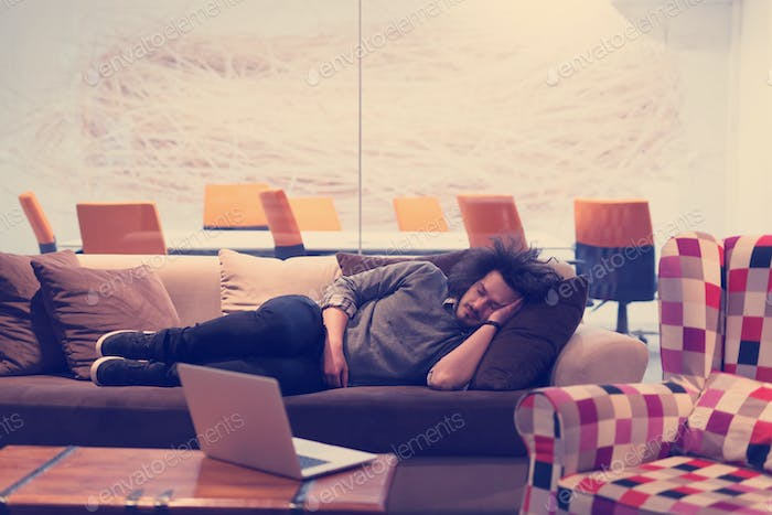 man sleeping on a sofa  in a creative office