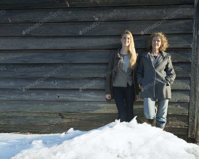 A mother and daughter standing leaning against barn, Snow piled up at their feet,