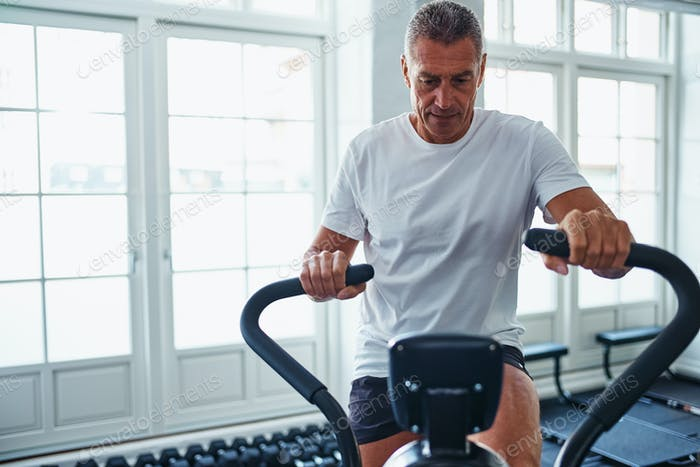 Mature man exercing on a stationary bike at the gym