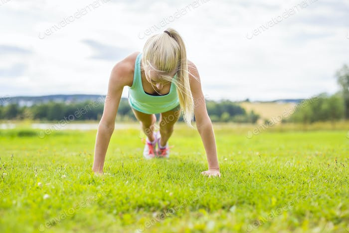 Young woman doing push-ups in the park
