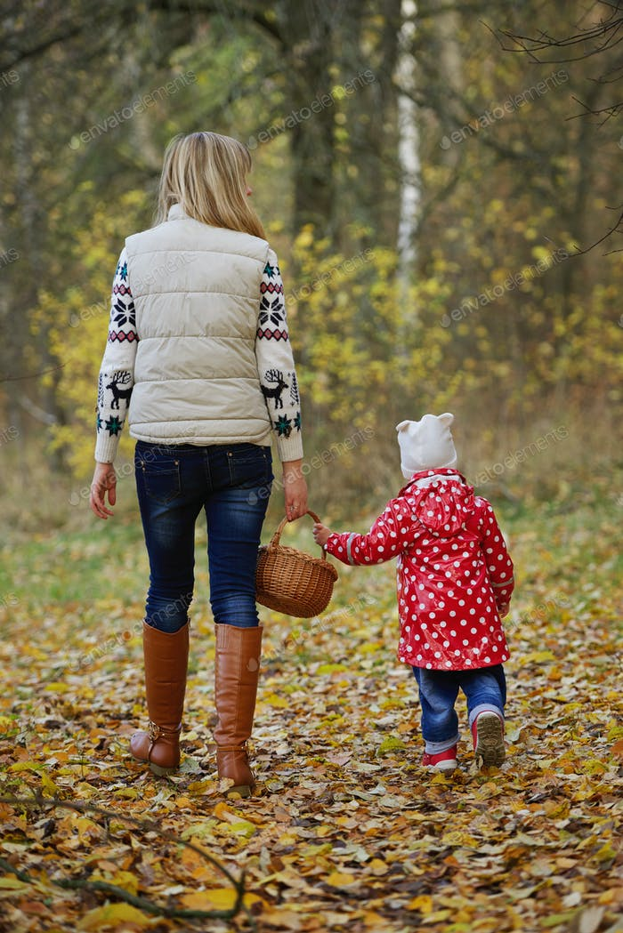 mother with daughter in autumn forest