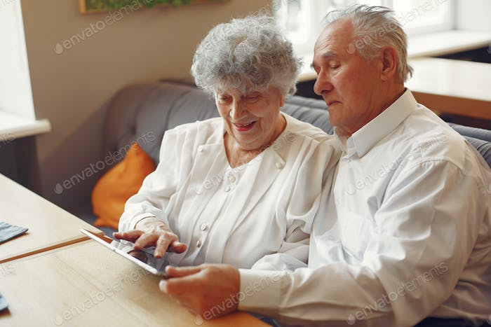 Elegant old couple in a cafe using a tablet