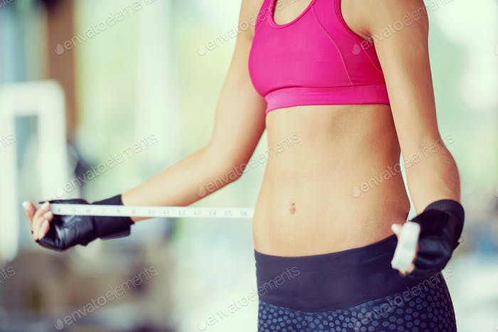 young fit woman measuring belly