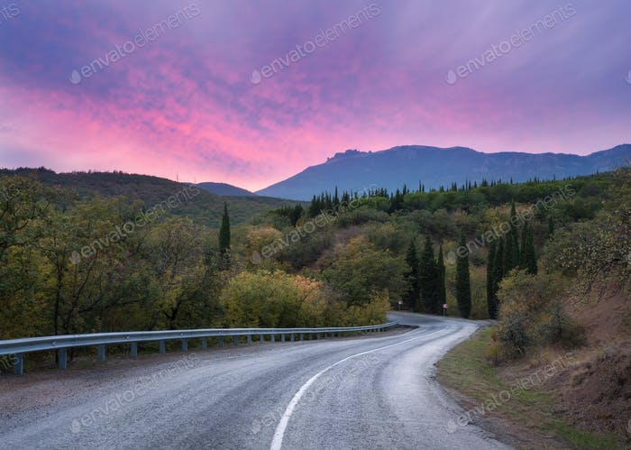Mountain road through the forest at colorful sunset. Travel back