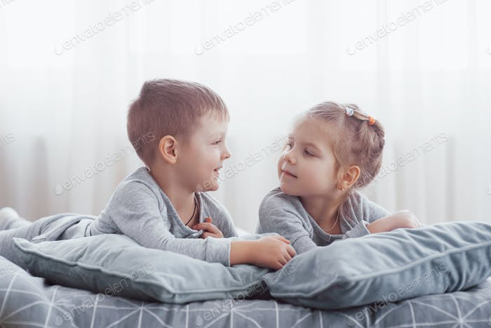 Boy and girl play in matching pajamas. Sleepwear and bedding for child and baby