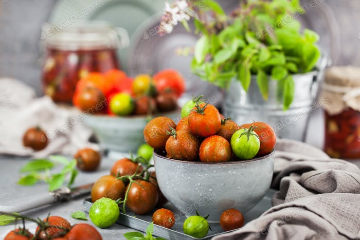 Fresh ripe cherry tomatoes in bowl on gray background