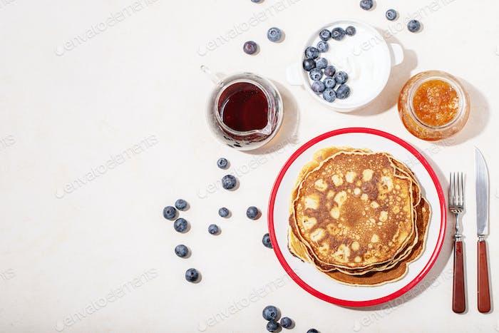 Ein Stapel von einfachen Pfannkuchen serviert mit Honig und Heidelbeere