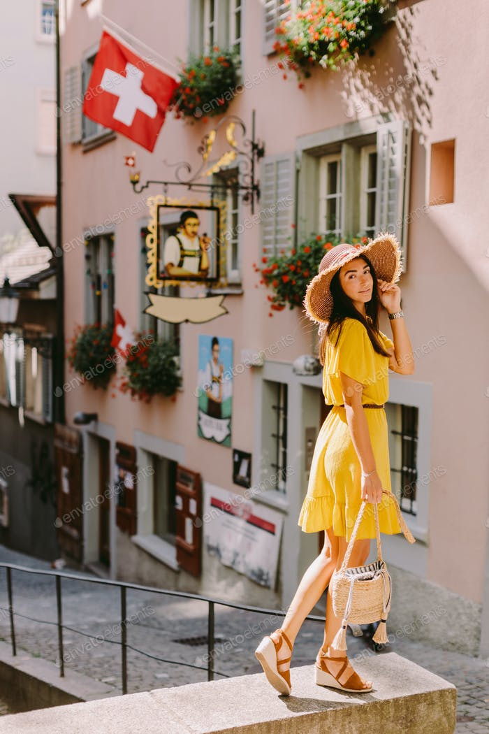 fashion woman wearing summer dress and straw hat posing outdoors